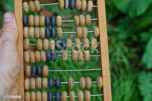 hand holds old brown wooden abacus on a green background