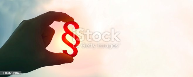 Hand holds paragraph symbol in the sun. Panoramic image with copy spae.