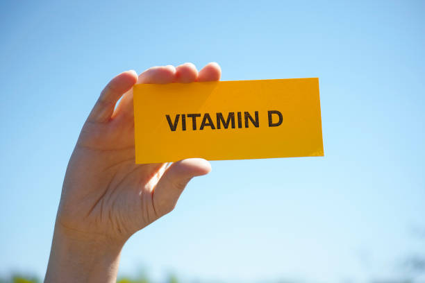 hand holds piece of paper with vitamin d against sunny blue sky - vitamin d стоковые фото и изображения