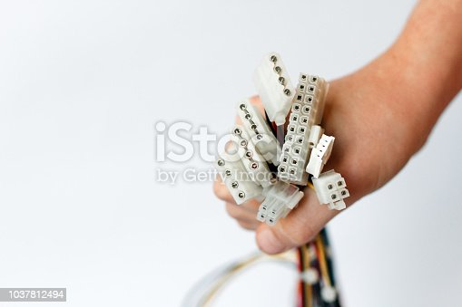 hand holds power cables from power supply unit on white background, PC motherboard power cables and connectors, 4pin peripheral connector, ATX 20+4 pin.