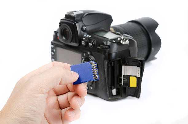 hand holds sd memory card and dslr camera on background - memory card stock photos and pictures