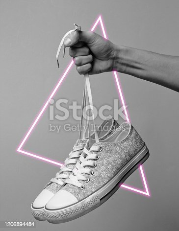 istock Hand holds sneakers by the laces. 80's synth wave and retrowave glowing triangle futuristic aesthetics. Old fashioned abstraction concept 1206894484