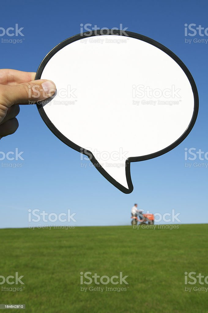 Hand Holds Speech Bubble Above Man Riding Lawnmower stock photo