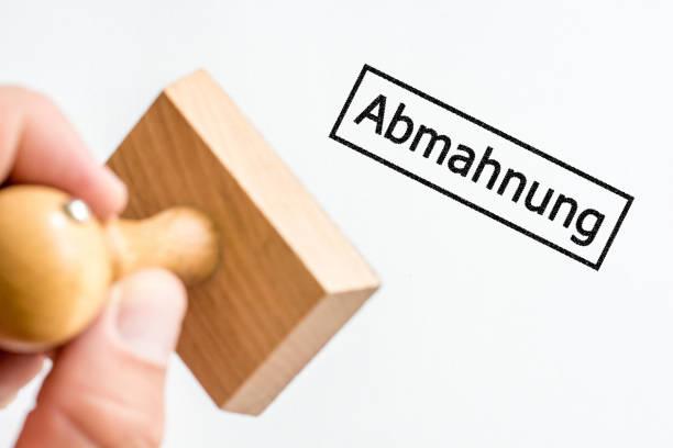 Hand hält Briefmarke mit Aufdruck in deutscher Sprache für Warnung – Foto