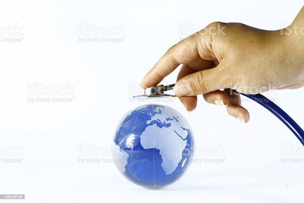 Hand holds stethoscope up to world globe Global Healthcare stock photo