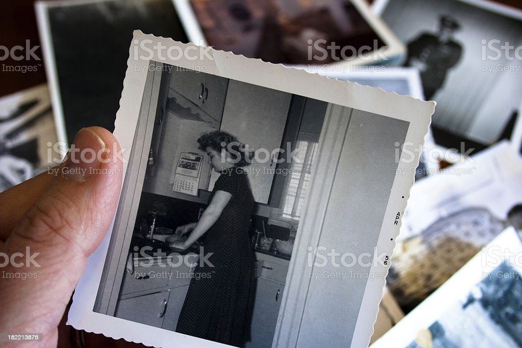 Hand holds Vintage photograph of 1950s woman in kitchen stock photo