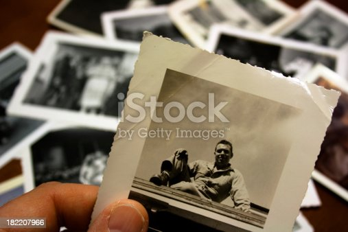 Hand holds vintage photograph of male with pile of old photos in background.  Please view my