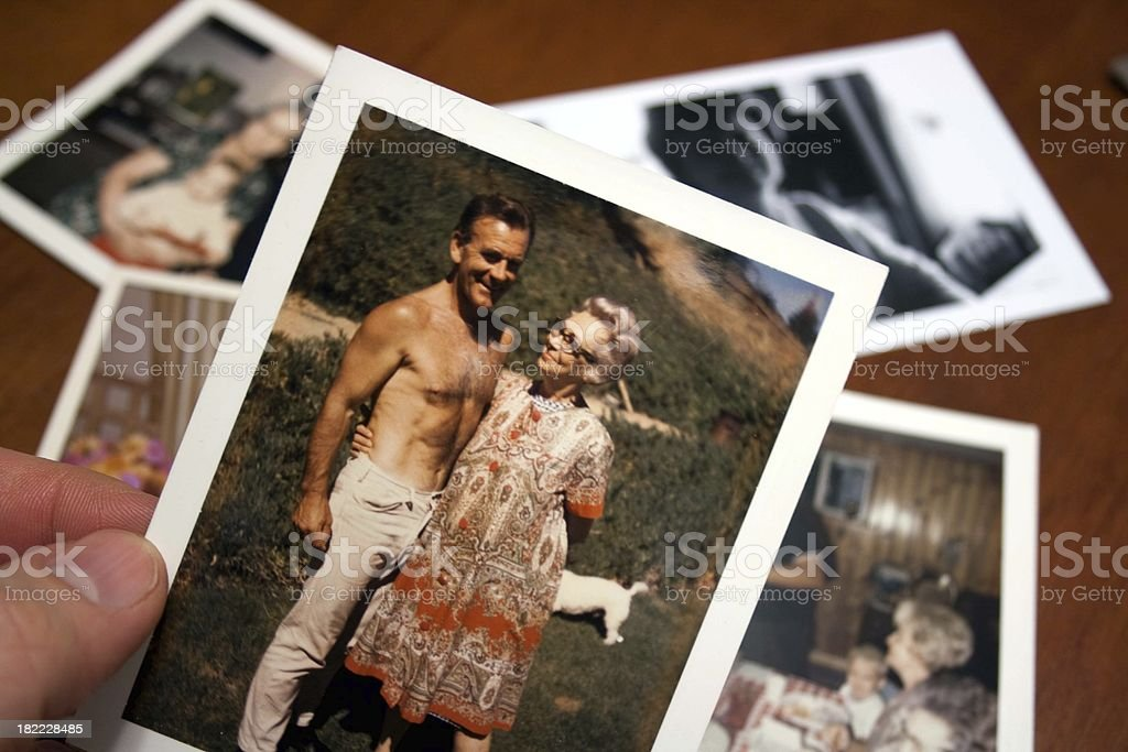 Hand holds Vintage photograph of 1960s husband and wife stock photo