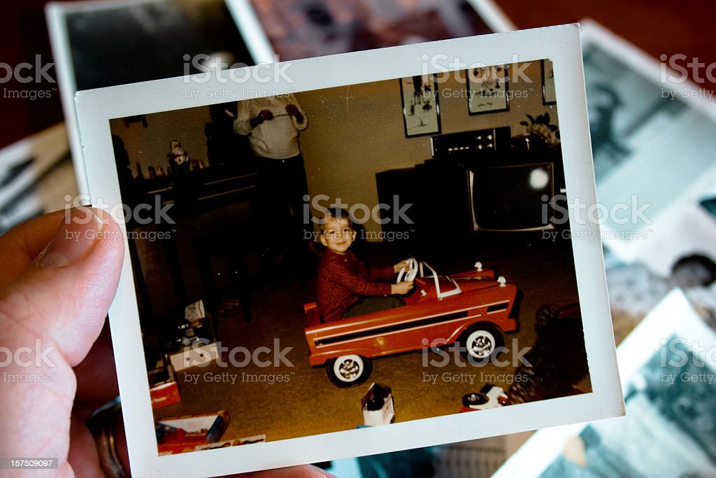 Hand holds Vintage photograph of boy in pedal car stock photo
