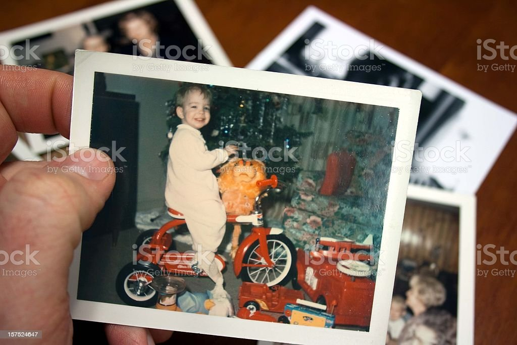 Hand holds Vintage photograph of boy on tricycle at christmas stock photo