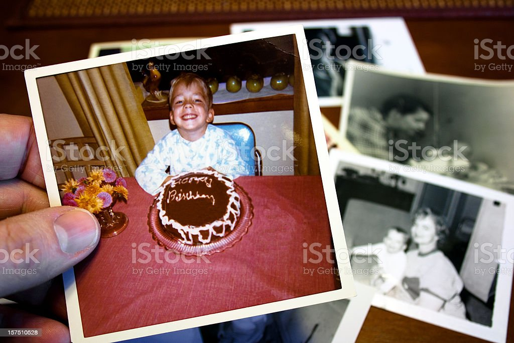 Hand holds Vintage photograph of child and birthday cake stock photo