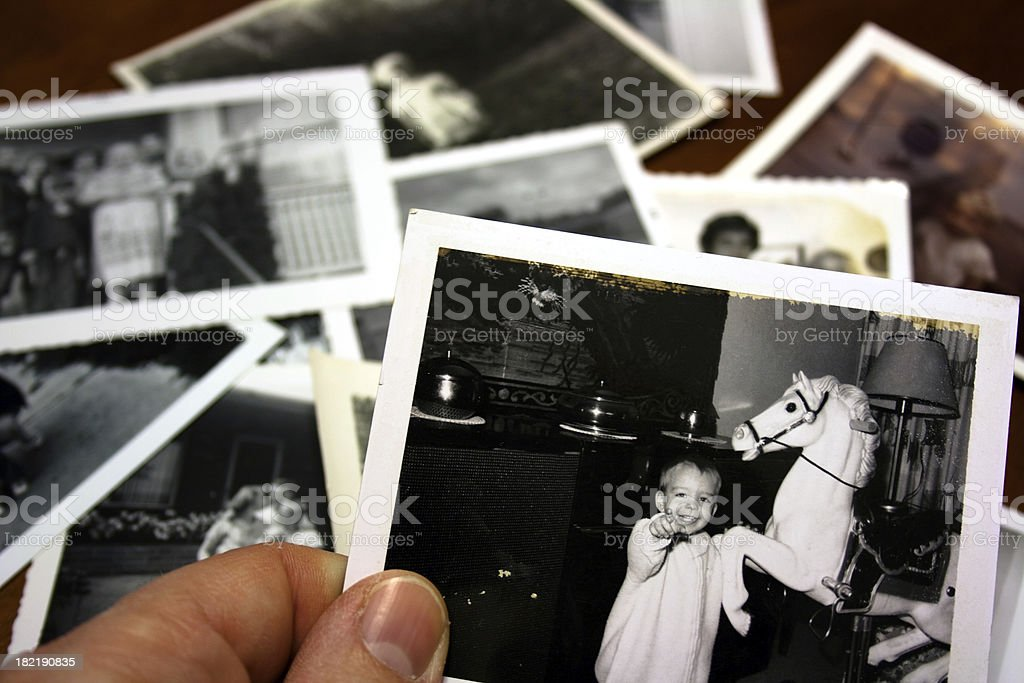 Hand holds Vintage photograph of child with hobby horse toy royalty-free stock photo