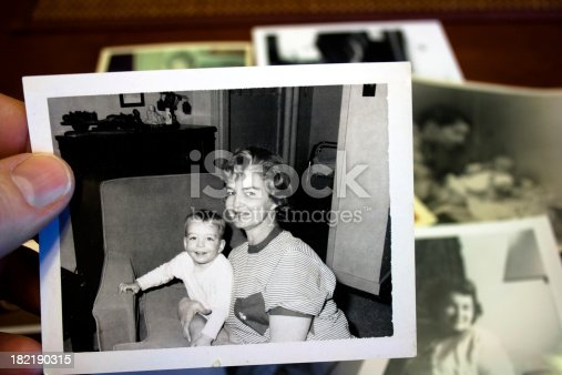 Hand holds vintage photograph of mother and child with pile of old photos in background.  Please view my