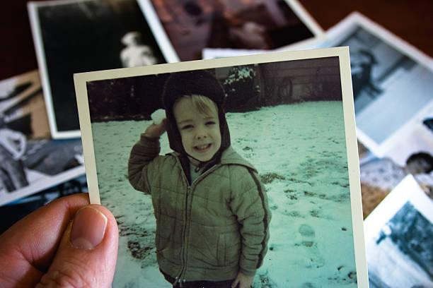 hand, die hält vintage foto mit jungen im schnee - kinder weihnachtsfilme stock-fotos und bilder