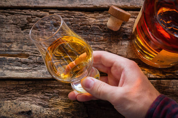 hand holds whiskey in a glass for tasting on a wooden background - assaggiare foto e immagini stock