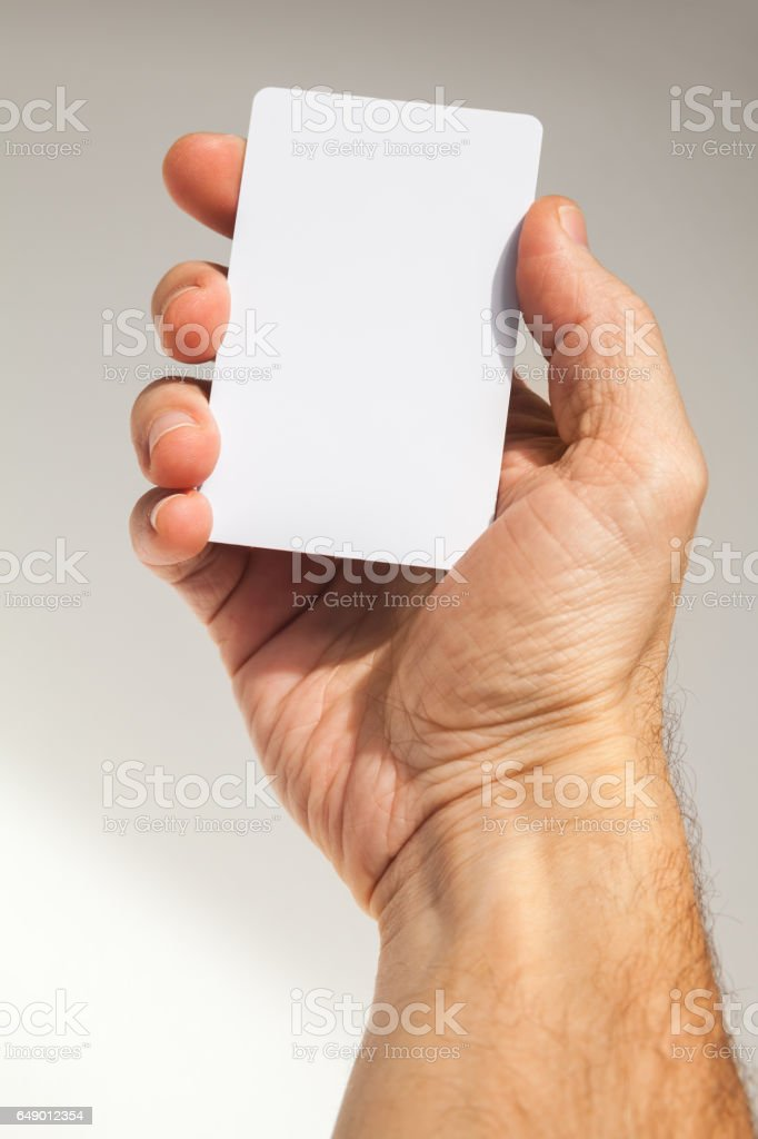 Hand holds white empty card over gray stock photo