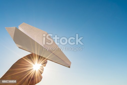istock Hand holds white paper plane on blue sky and sun 688236858