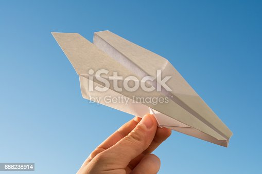 658921430 istock photo Hand holds white paper plane on blue sky 688238914