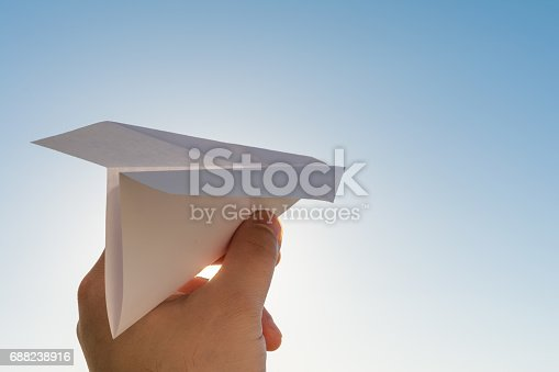 istock Hand holds white paper plane on blue sky 688238916