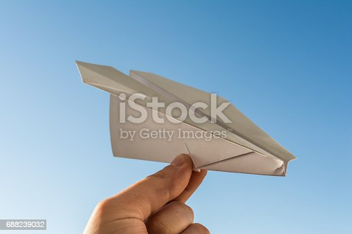 658921430 istock photo Hand holds white paper plane on blue sky 688239032