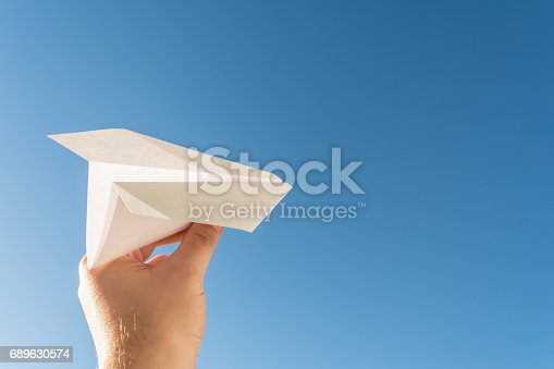 istock Hand holds white paper plane on blue sky 689630574