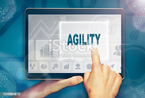 istock A hand holiding a computer tablet and pressing a agility concept. 1049964610