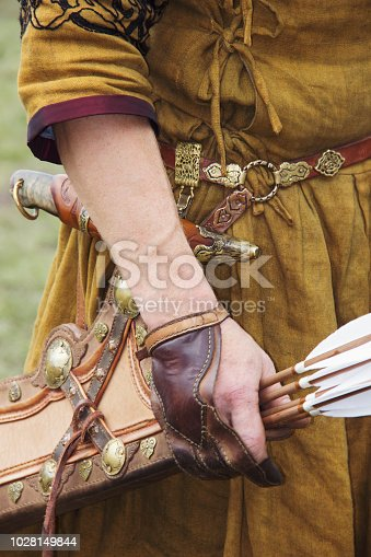 istock Hand in a beige cloak holds Quiver with arrows in a quiver on a green background. 1028149844