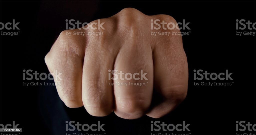Hand in a fist shape punching close to the camera lens stock photo