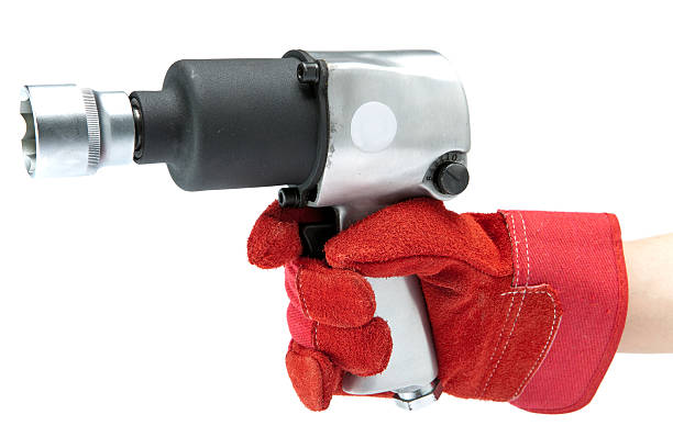 Hand in a red working glove holding an air impact wrench