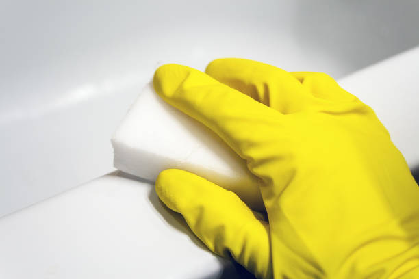 Une main dans un gant en caoutchouc jaune essuie la surface d'un bain blanc avec une éponge à mélamine. Nettoyage dans une salle de bains moderne. Mise au point sélective. Vue de plan rapproché - Photo