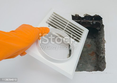 1132163701istockphoto Hand in an protective rubber glove cleans clogged air duct grille at home. Cleaning service concept. 1128294510