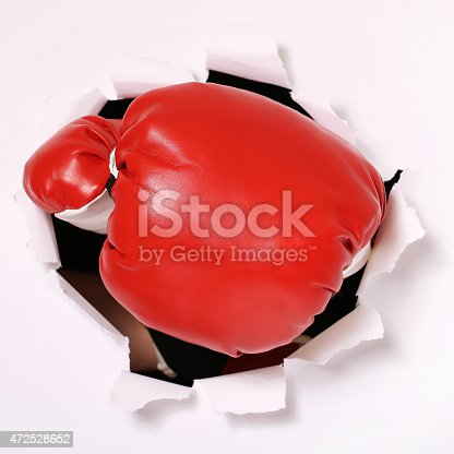 160558362 istock photo Hand in boxing glove through paper hole 472528652