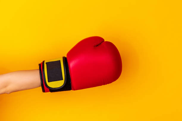 Hand in boxing red glove isolated on yellow studio background with copyspace. stock photo