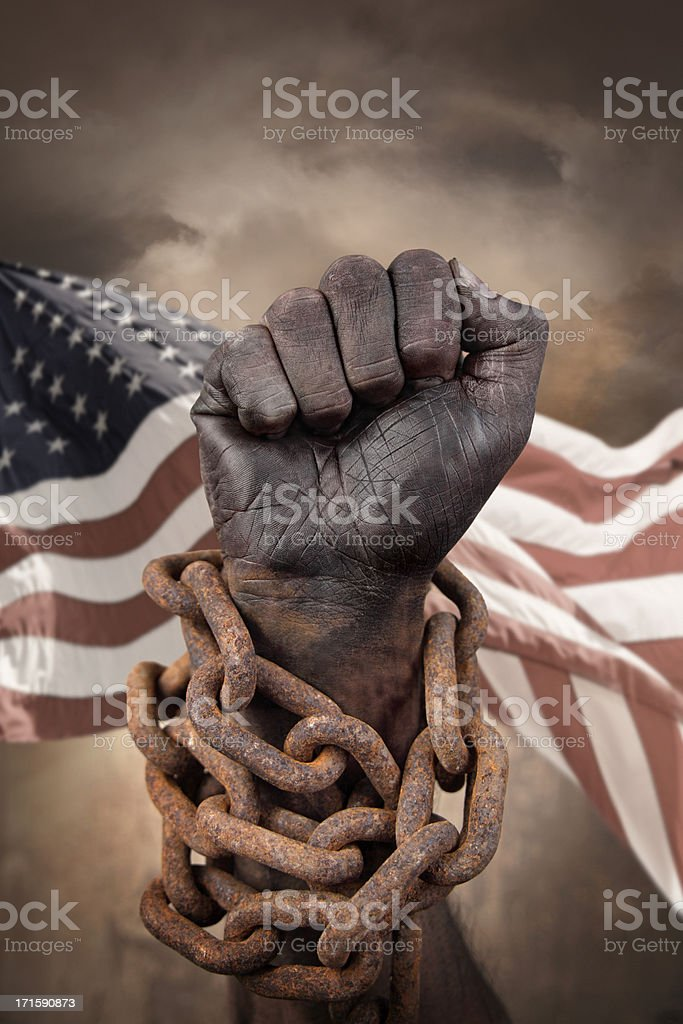 Hand in chains with US flag behind stock photo