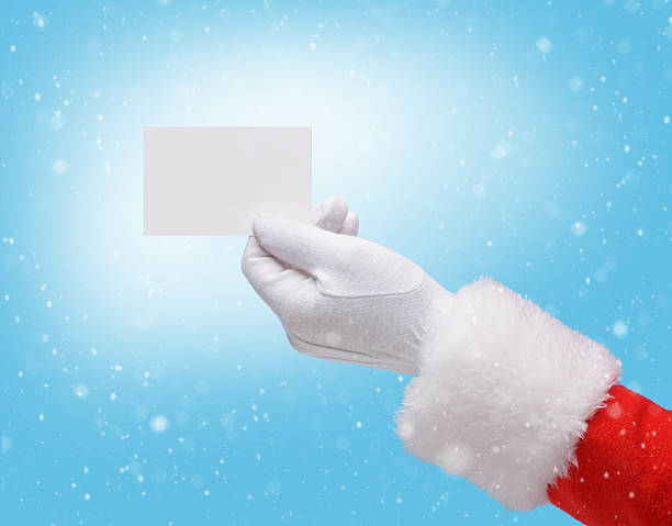 hand in costume santa claus is holding business card - gift voucher or card stock photos and pictures