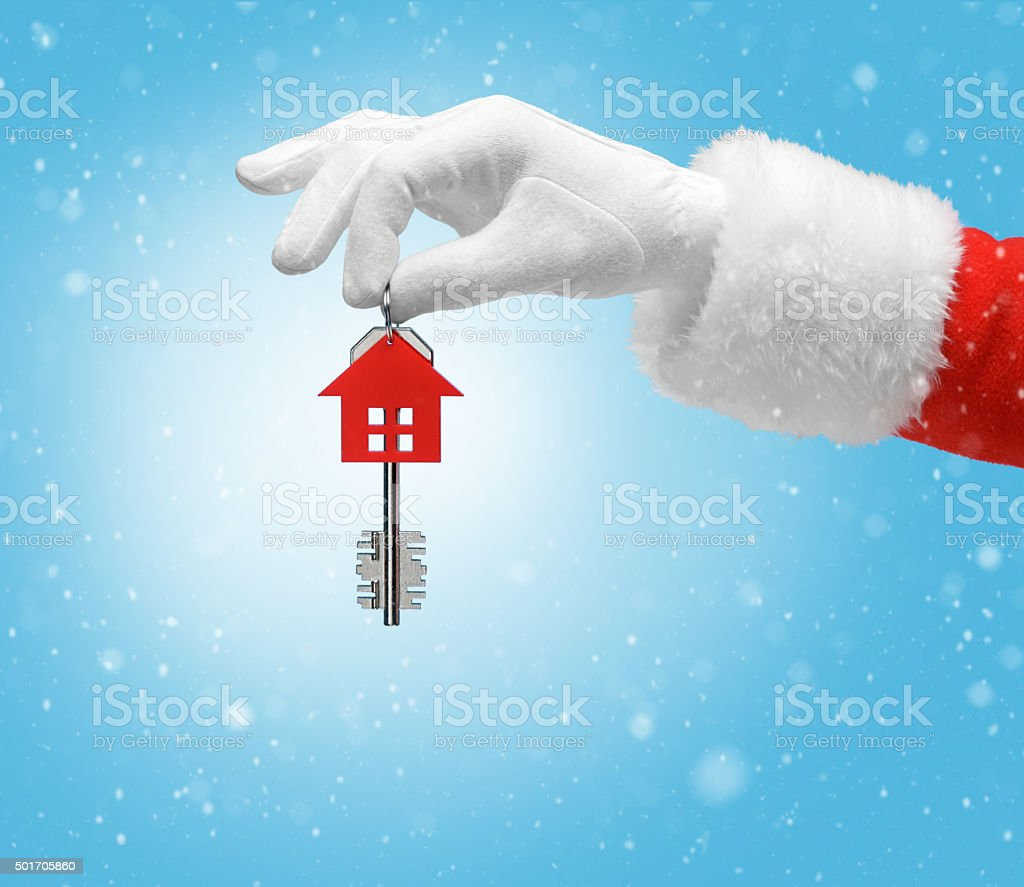 Hand in costume Santa Claus is holding house keys stock photo