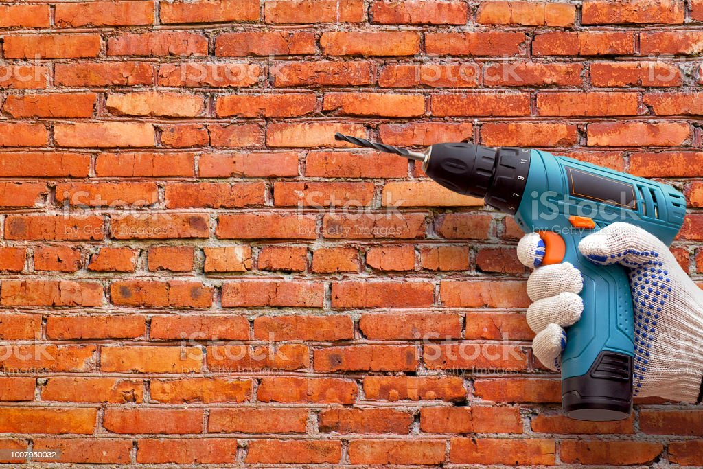 Hand In Dotted Work Glove Holding Cordless Drill Machine On Brick