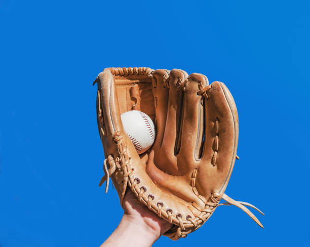 Hand in glove for a baseball game caught a leather white ball on a blue sky background. Sports contests. Victory. Achievement of success. stock photo
