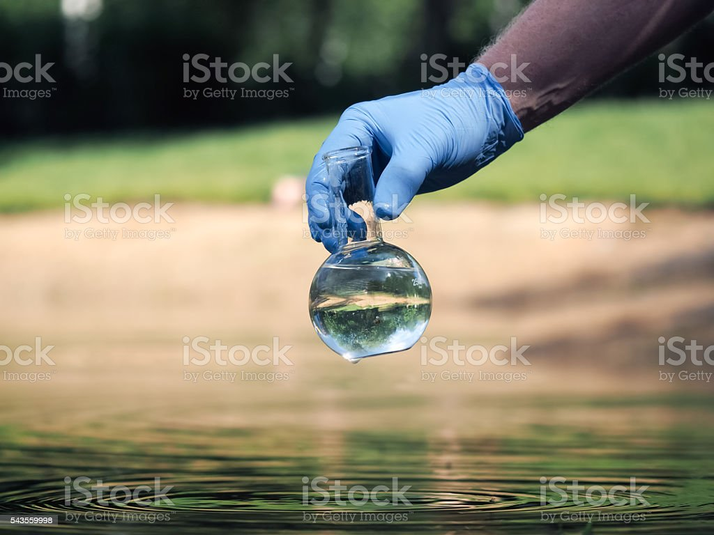 Hand in glove holding a retort with clear water стоковое фото