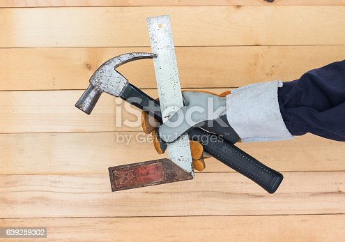 istock Hand in glove holding iron ruler and hammer 639289302