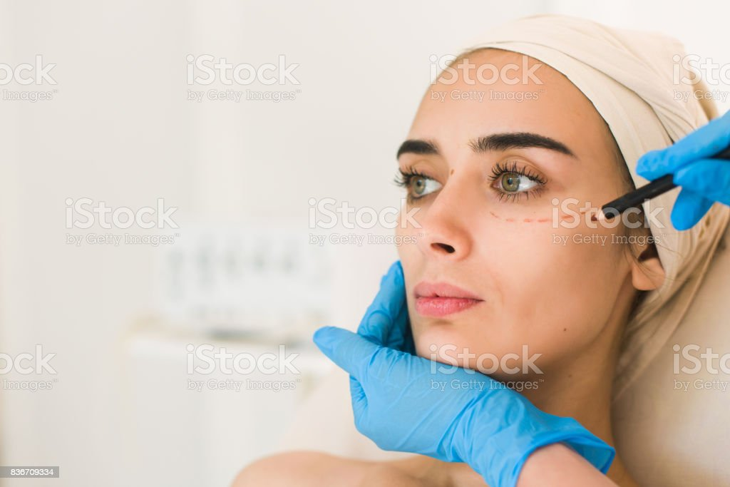 Hand in glove marking women face. stock photo