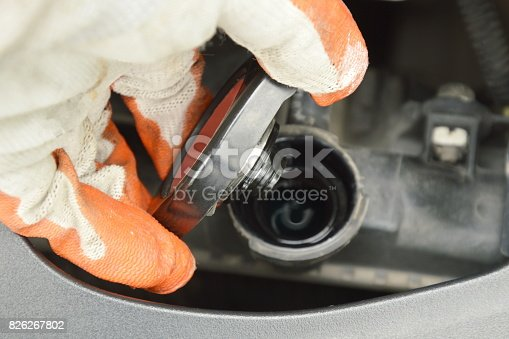 hand in glove open car radiator cover and checking water level for safety