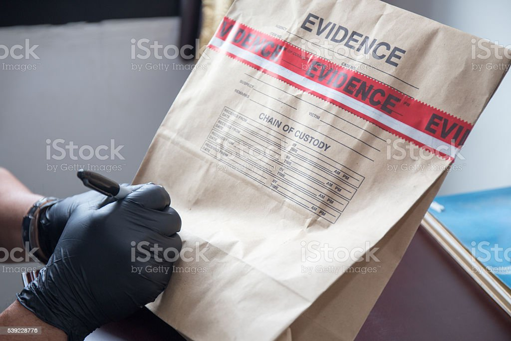 hand in glove writing on sealed evidence bag stock photo