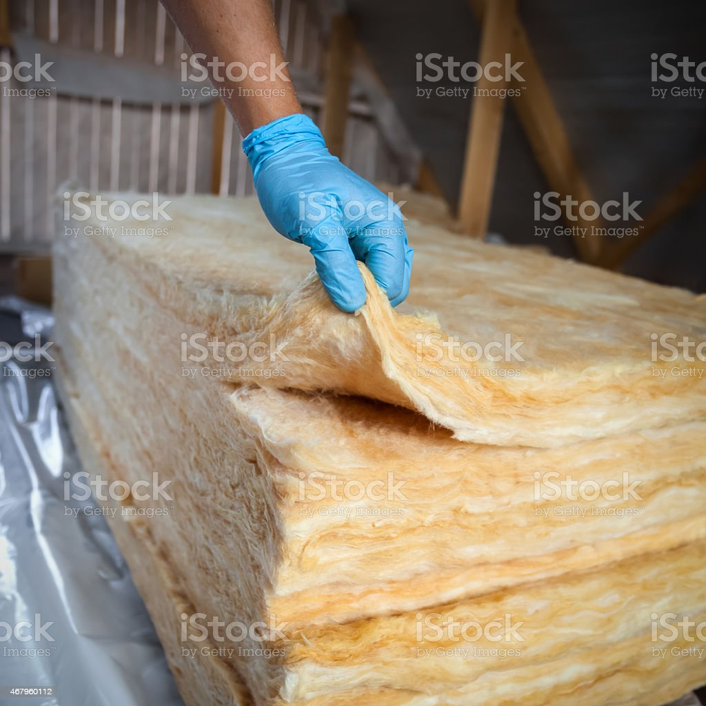 Hand in gloves holding mineral wool stock photo