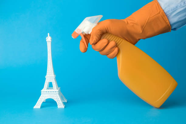 Manos con guantes usando desinfectante para desinfectar la Torre Eiffel. Francia y el virus covid-19 pandémicos abstractos. - foto de stock