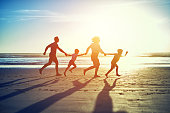 Shot of a carefree family of four enjoying a run on the beach