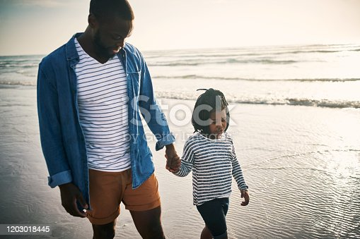 Shot of a young man spending time at the beach with his adorable daughter