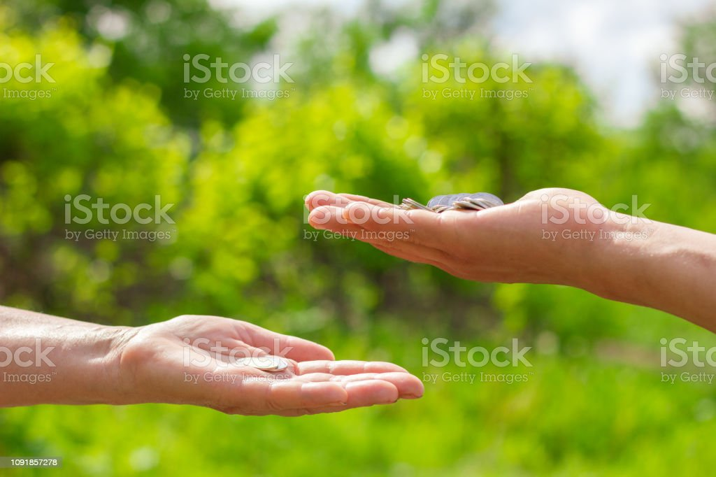 hand in hand gives coins on green background, Finance concept and...
