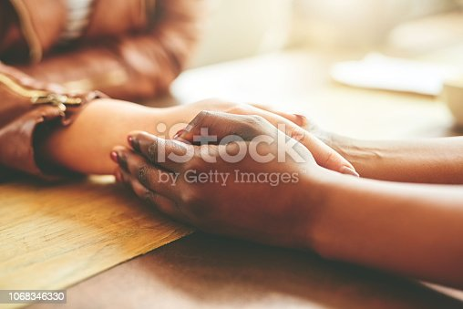 High angle shot of two female friends holding hands in comfort while sitting in their local coffee shop