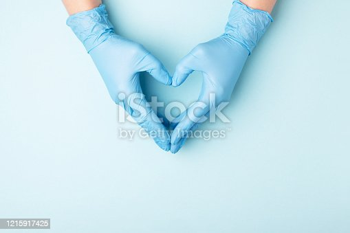 Doctor's hands in medical gloves in shape of heart on blue background with copy space.
